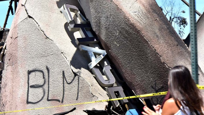 The Chase Bank sign is located in the rubble of a burning building that was attacked by protesters.