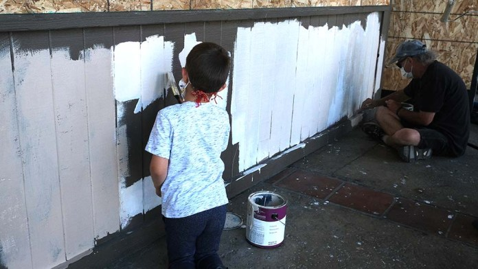 Family members showed up at the La Mesa Springs Shopping Center Sunday morning to paint, clean and climb broken windows.