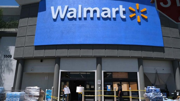 Walmart employees hold a sign that says the shop was closed after being looted the night before.