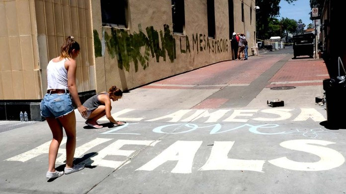 Grossmont High School student Sofia Kruse, 15, and Meakalia Gilnan (kneeling), 16, made a chalk message that read
