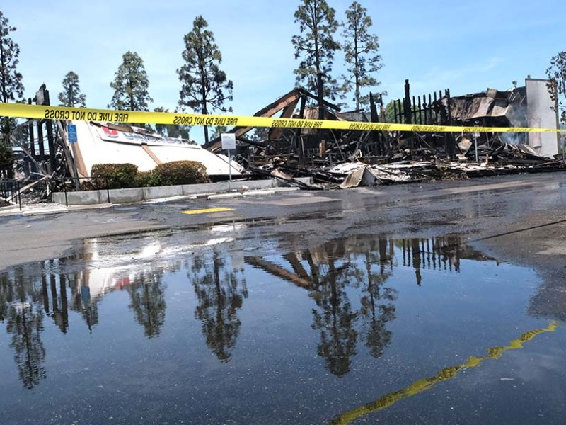 A burned Union Bank that was still smoldering after a night of violence in La Mesa is reflected in water from firemen's hoses.