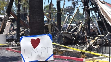 A pro-police poster is tasked up in front of a Union Bank that was burned to the ground by protestors in downtown La Mesa.