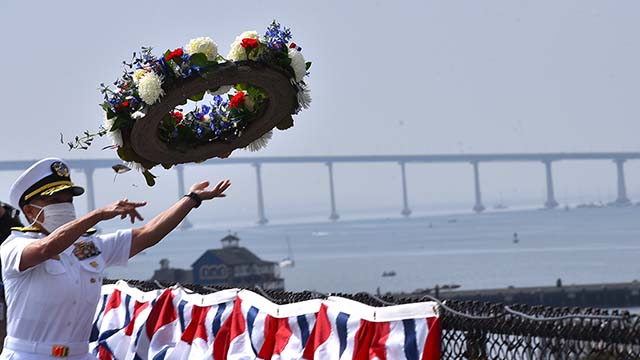 Rear Adm. Bette Bolivar, commander of Navy Region Southwest, tosses a wreath from the USS Midway into San Diego Bay. Photo by Chris Stone