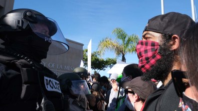 A protester and La Mesa police officer face off near entrance of police station.