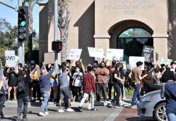 Marchers cross near northwest corner of La Mesa police station.