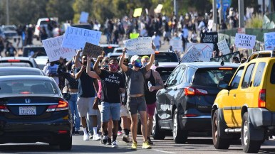 Protesters thread their way through blocked Interstate 8 traffic in La Mesa.