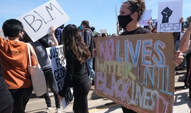 """A woman holds a sign saying: """"No lives matter until black lives do."""""""