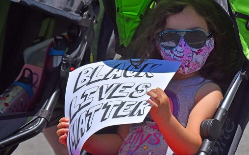 A young girl with her family holds a supporting sign in the La Mesa Police Department parking lot.