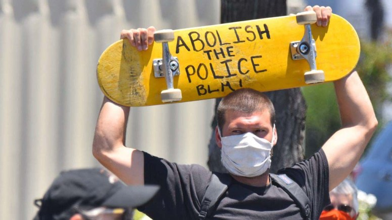 A protester shows his support with his skateboard. Photo by Chris Stone