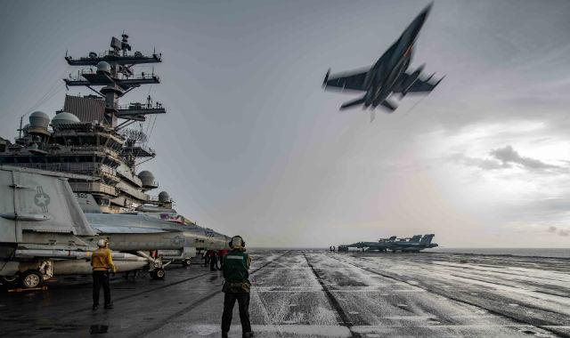 F/A-18E Super Hornet passes over the USS Ronald Reagan