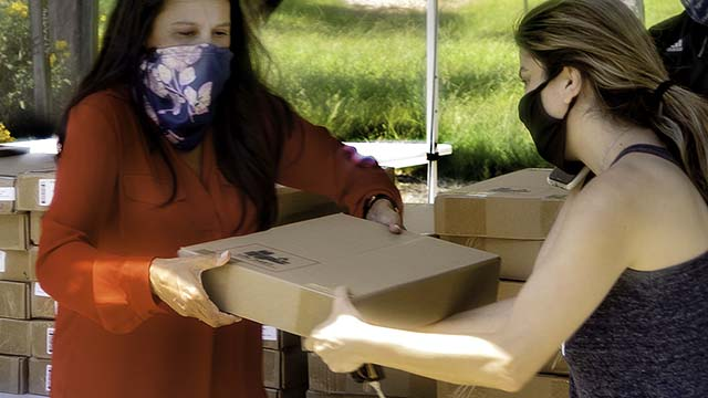 Cuyamaca College President Julianna Barnes (left) helps distribute laptops this summer to students who were economically affected by the pandemic. More laptops are being distributed this fall to students in the region.