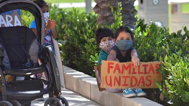 Children hold signs calling for the unification of separated immigrant families.