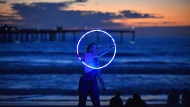 A woman spins a lit up hula hoop on the beach near Ocean Beach Pier.