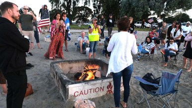 Genevieve Peters (center) speaks to about two dozen anti-mask proponents at a mask-burning event.