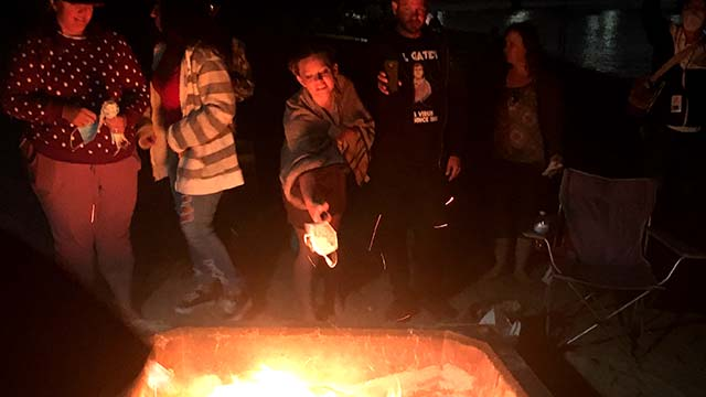 An anti-mask proponent tosses a KN95 mask into a fire pit at Mission Bay.
