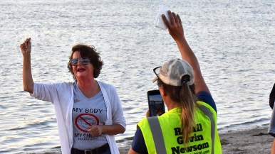 Genevieve Peters (left) speaks as a anti-mask proponent holds up a mask that she later burned.