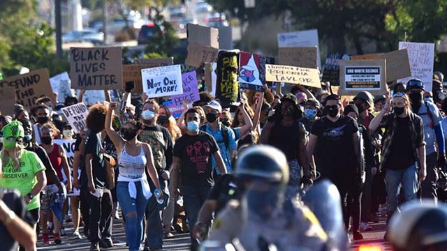 Protesters block intersection of La Mesa Boulevard and University Avenue on the way back from a winding march through a hilly La Mesa neighborhood.