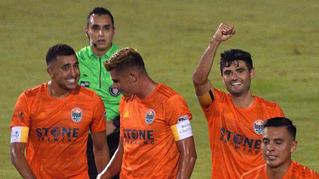 Alejandro Guido (second from right) cheers as he scores his second goal of the match against Orange County.