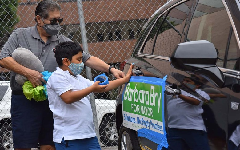 Richard Ybarra and his grandson, Rex, 9, prepare their SUV for a caravan for mayoral candidate Barbara Bry. Ybarra was son-in-law of Cesar Chavez.
