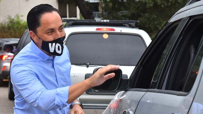 Assemblyman Todd Gloria waves to volunteers in the back seat of a SUV who came to help canvass for his mayoral campaign.