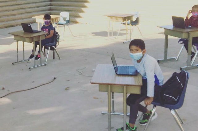 Students working on computers outside