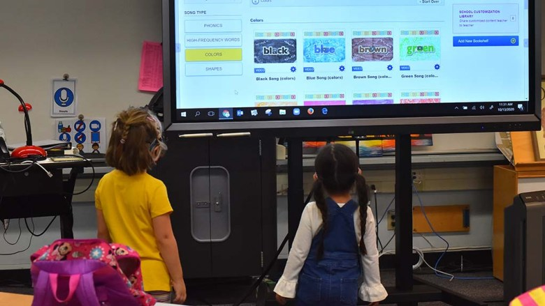 Two students watch a smart board in their classroom on the first day back to school.