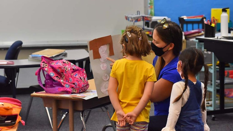 A teacher looks over a students number chart at Lafayette Elementary School on the first day of limited on campus instruction.