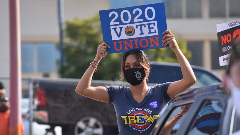 IBEW Local 465 organizer Anabel Arauz shows her support for Democratic candidates downtown on Election Day.