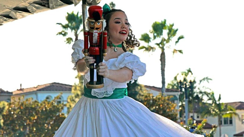 Vanessa Schroeder, a student at the San Diego Ballet School, holds out a nutcracker as she plays Clara in the Nutcracker performance at Liberty Station.