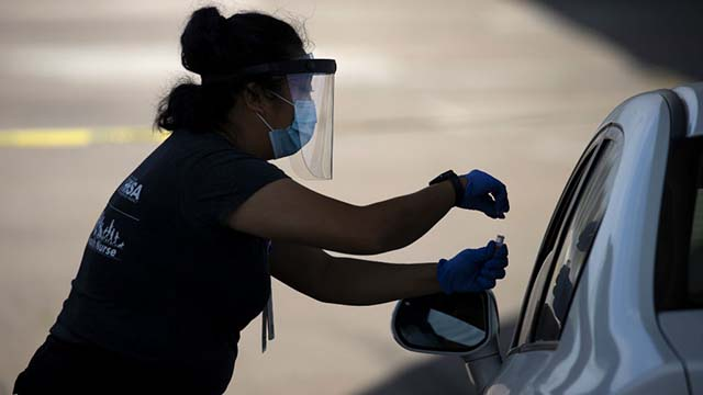 A San Diego County health nurse collects a sample from a patient at a drive-in COVID-19 testing site. REUTERS/Mike Blake