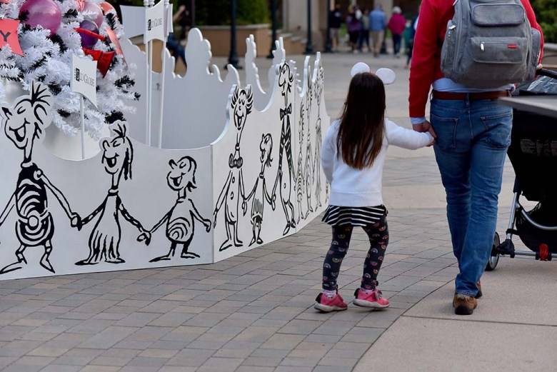 A girl holds hands with her father as she passes by the sketches of the Whos hand-in-hand.