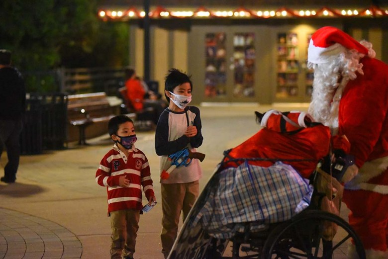 Children stop to get a small gift from Santa a.k.a. Joseph Taylor who lives in downtown San Diego.
