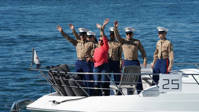 Marines wave to spectators near the USS Midway during a boat parade in San Diego Bay on Veterans Day 2020