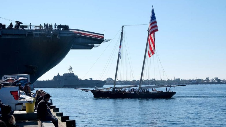 """Active duty members sail in the Yacht """"America"""" during the Veterans Day boat parade in San Diego Bay."""