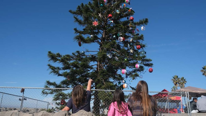 Visitors to the beach check out the ornaments added to the Ocean Beach Christmas tree on Dec. 2.