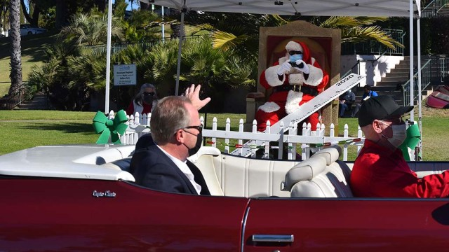 Mayor Kevin Faulconer waves at Santa (aka Bill Swank) at Taste of December Nights after the opening ceremony.