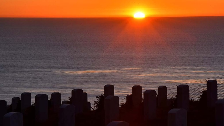 Sun sets on Fort Rosecrans National Cemetery on Wreaths Across America Day.