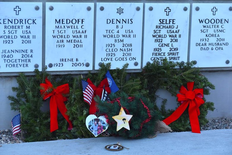 Holiday ornaments and evergreen branches with garland were placed at a name plate at Fort Rosecrans National Cemetery.