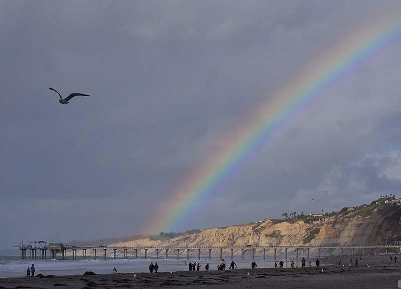A rainbow develops as sun shines on the hillsides by Scripps Pier in La Jolla.