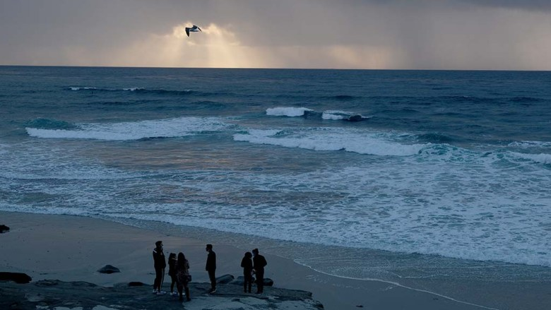 A group of young people look out over the ocean at Windansea as rain falls in the distance.
