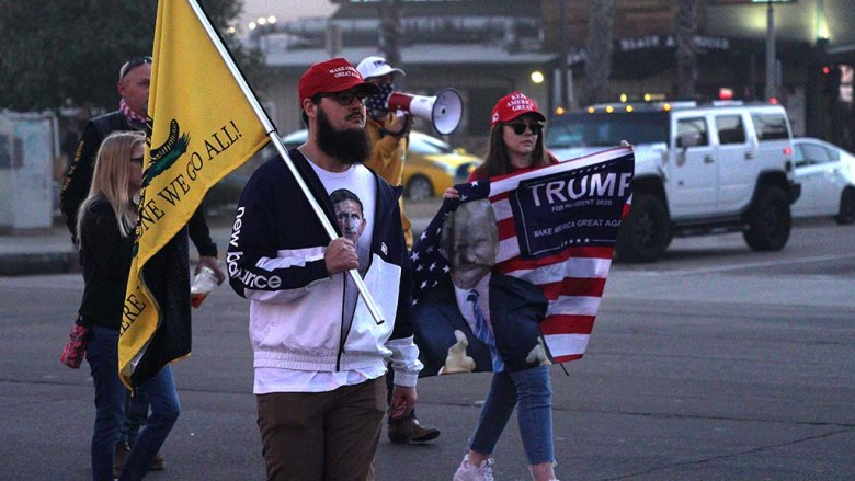 Trump supporters carry flags as they walk along Mission Boulevard in Pacific Beach.