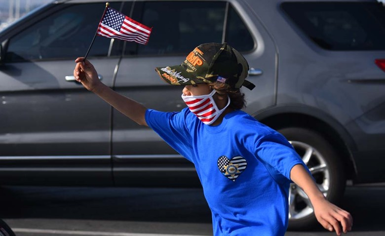 A young boy skates in a parking lot across from the San Diego County Administration Building, showing his support for the president.