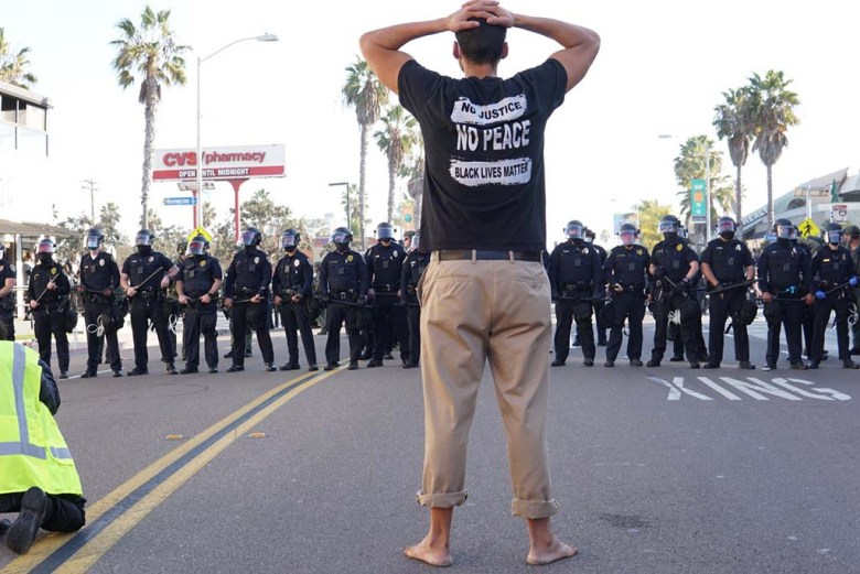 Counterprotester in Black Lives Matter shirt faces police line in Pacific Beach.