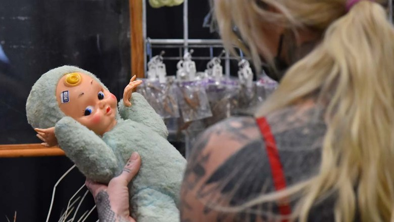 A tattooed women buys a doll at a booth at the Oddities and Curiosities Fair in Del Mar.