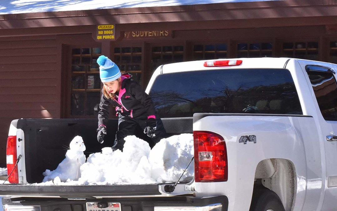 A young girl help pack up piles of snow in the back of a pickup for the road home.
