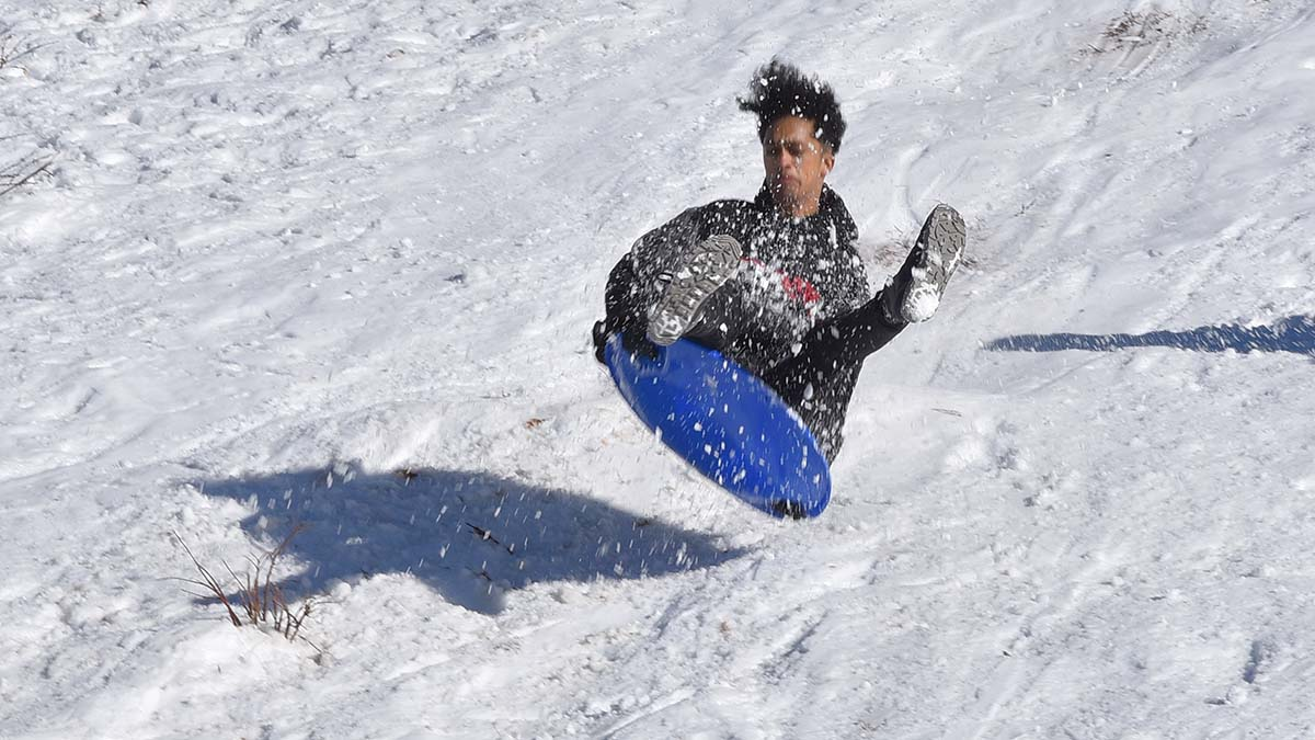 A sledder took flight on the rapid descent down the snowy hill in Mt. Laguna.