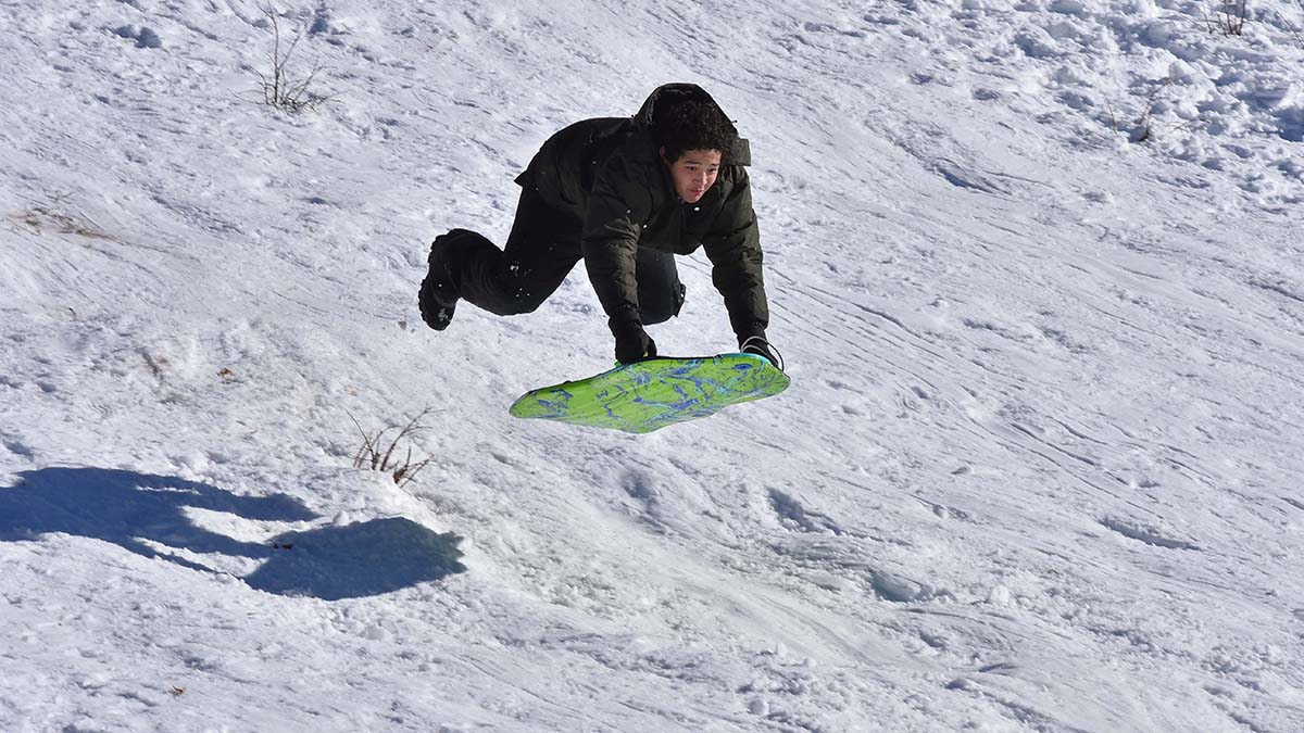 One sledder catches more air than he expected as he descends down the bumpy hill.