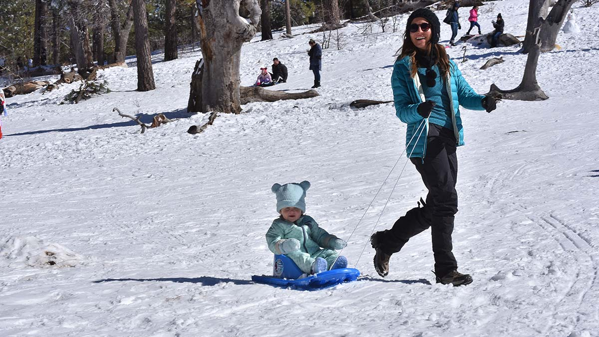A baby gets a taste of snow with the help of mom.
