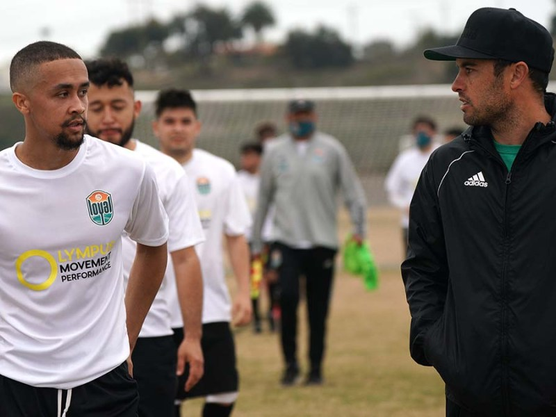 Brendan Hildreth of Seattle (left) speaks with San Diego Loyal Team Manager Landon Donovan after a tryout session.