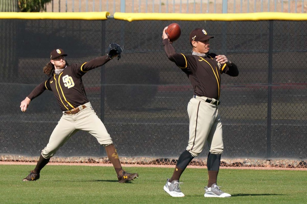 While Chris Paddack (left) hurls a pitch, Keone Kela warms up with a football.